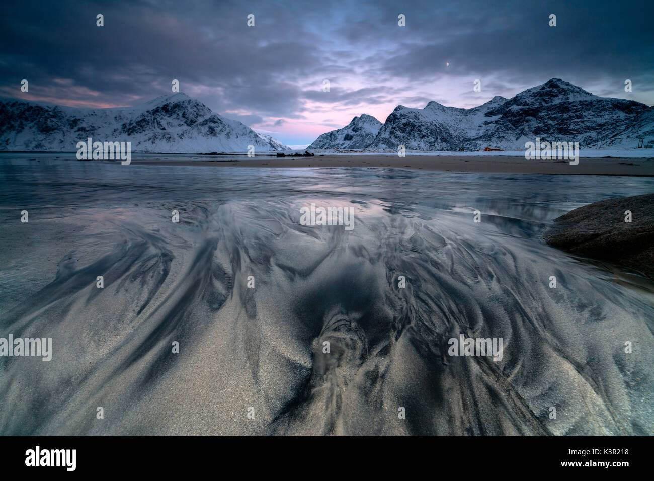 Wellen und Eis auf den surrealen Skagsanden Strand umgeben von schneebedeckten Gipfeln Flakstad Nordland county Lofoten Inseln Norwegen Europa Stockbild