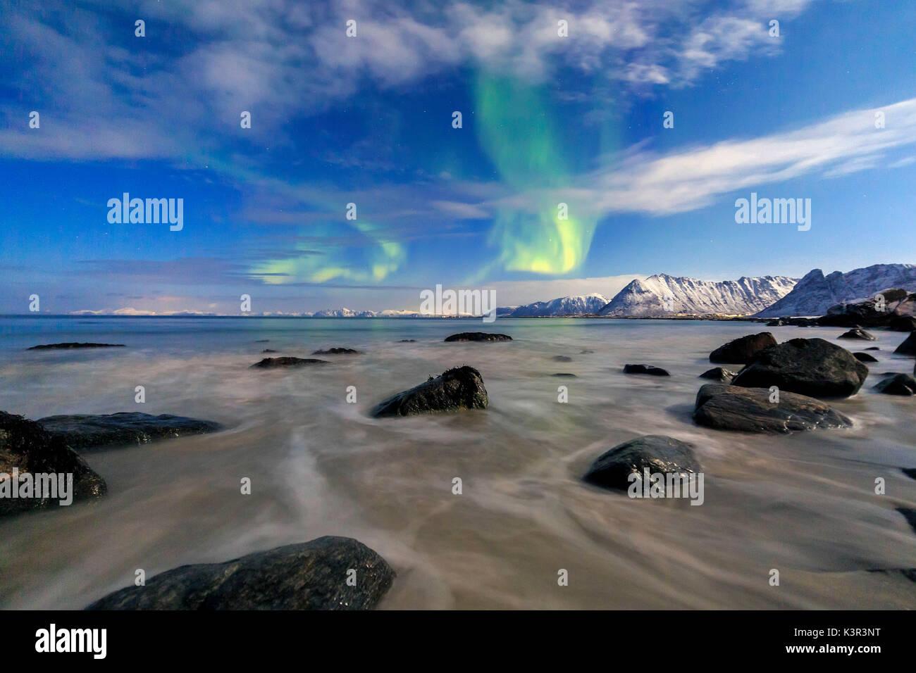 Northern Lights die Landschaft um Gymsøyand und die schneebedeckten Gipfel beleuchten. Lofoten in Nordnorwegen Europa Stockbild