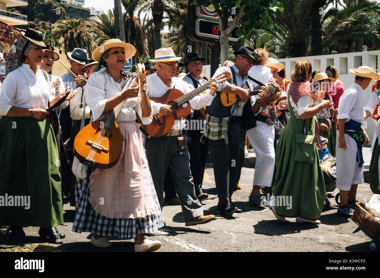 Puerto de la Cruz, Teneriffa, Kanarische Inseln - 30. Mai 2017: Kanaren Menschen in traditionellen Kleidern bekleidet Spaziergang entlang der Straße, Zeichen und Spielen musica Stockbild