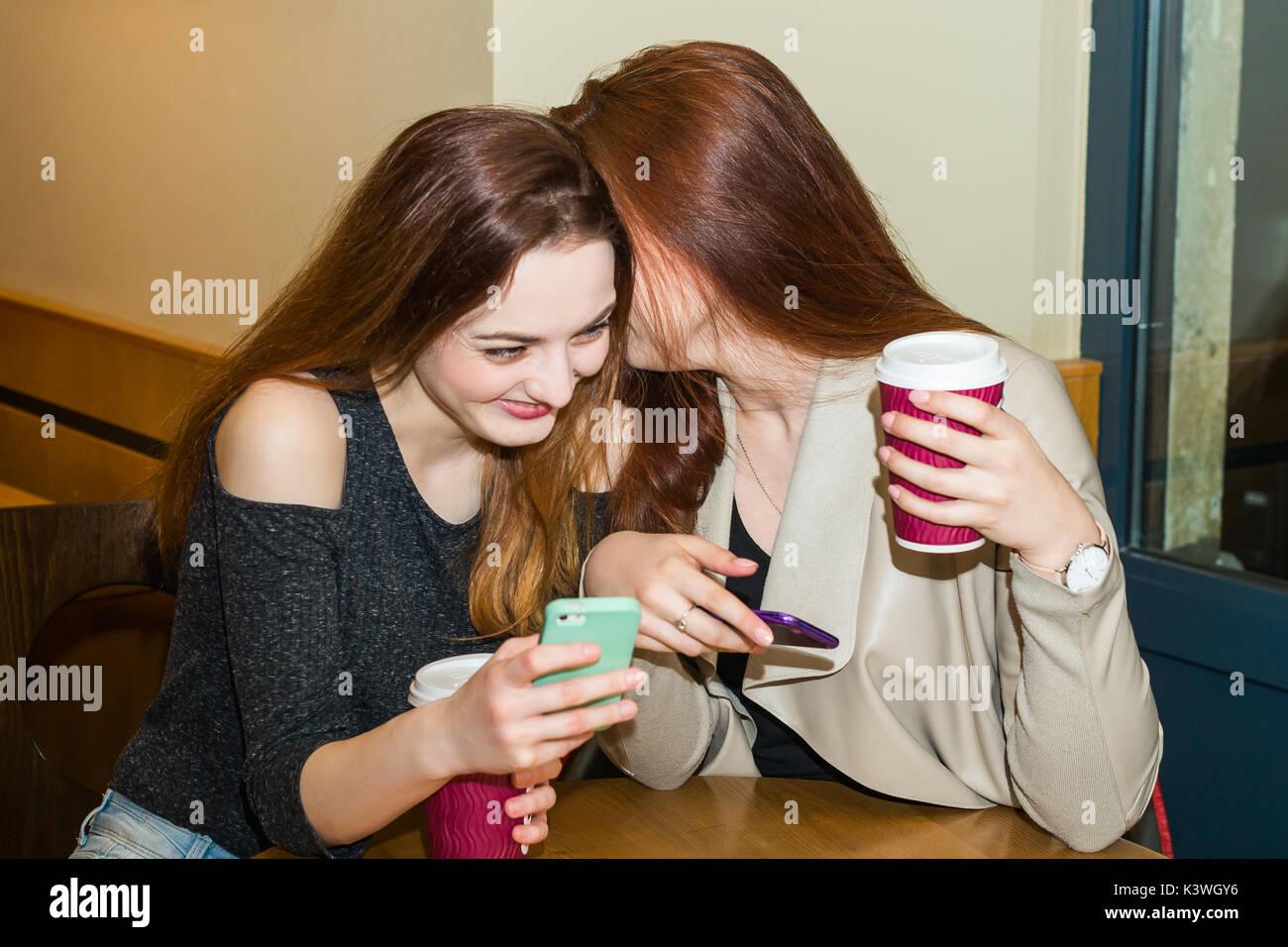 Zwei Mädchen tratschen in einem Cafe Bar Stockbild