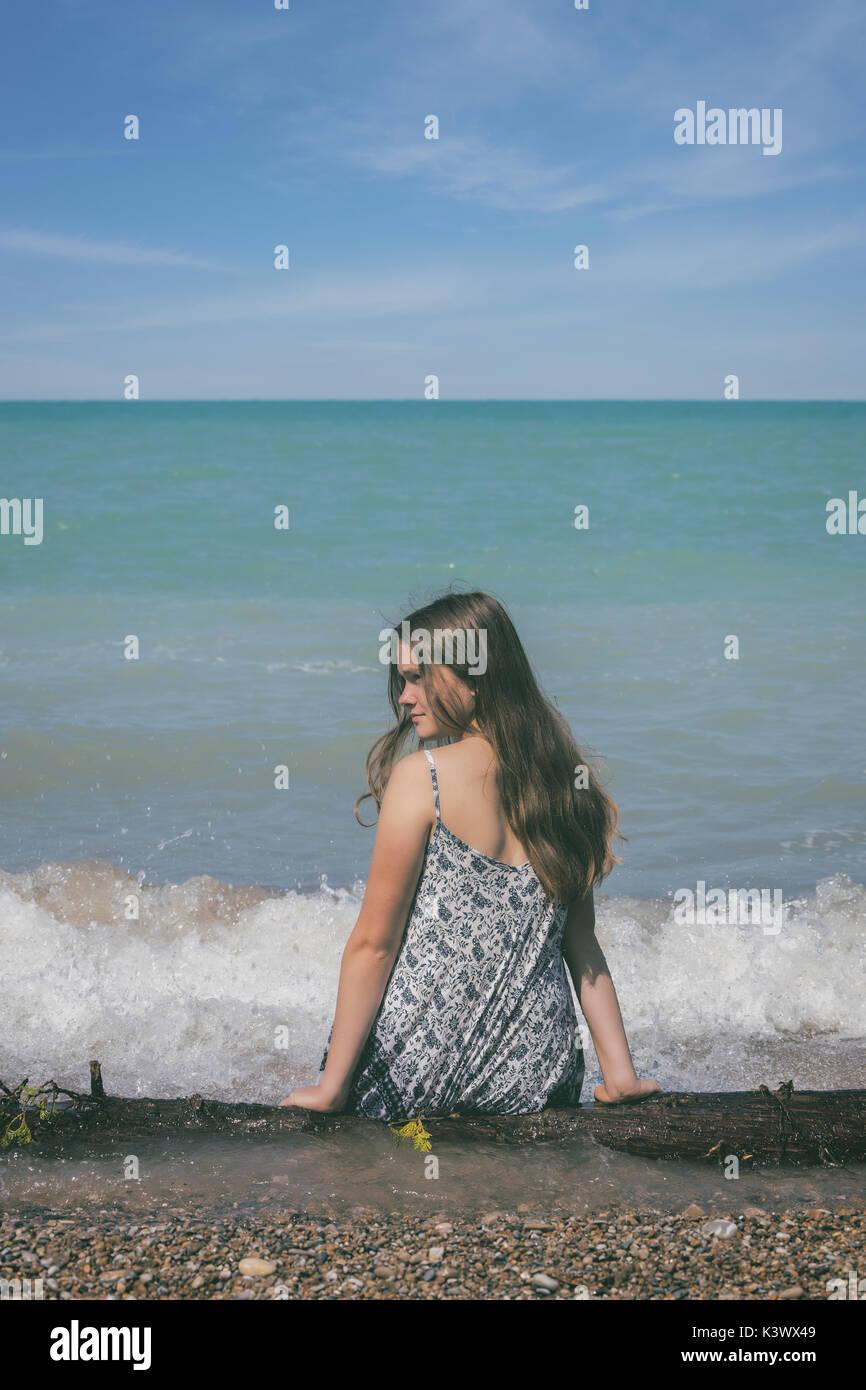 Ein Mädchen sitzen auf ein Protokoll auf einem See Stockfoto
