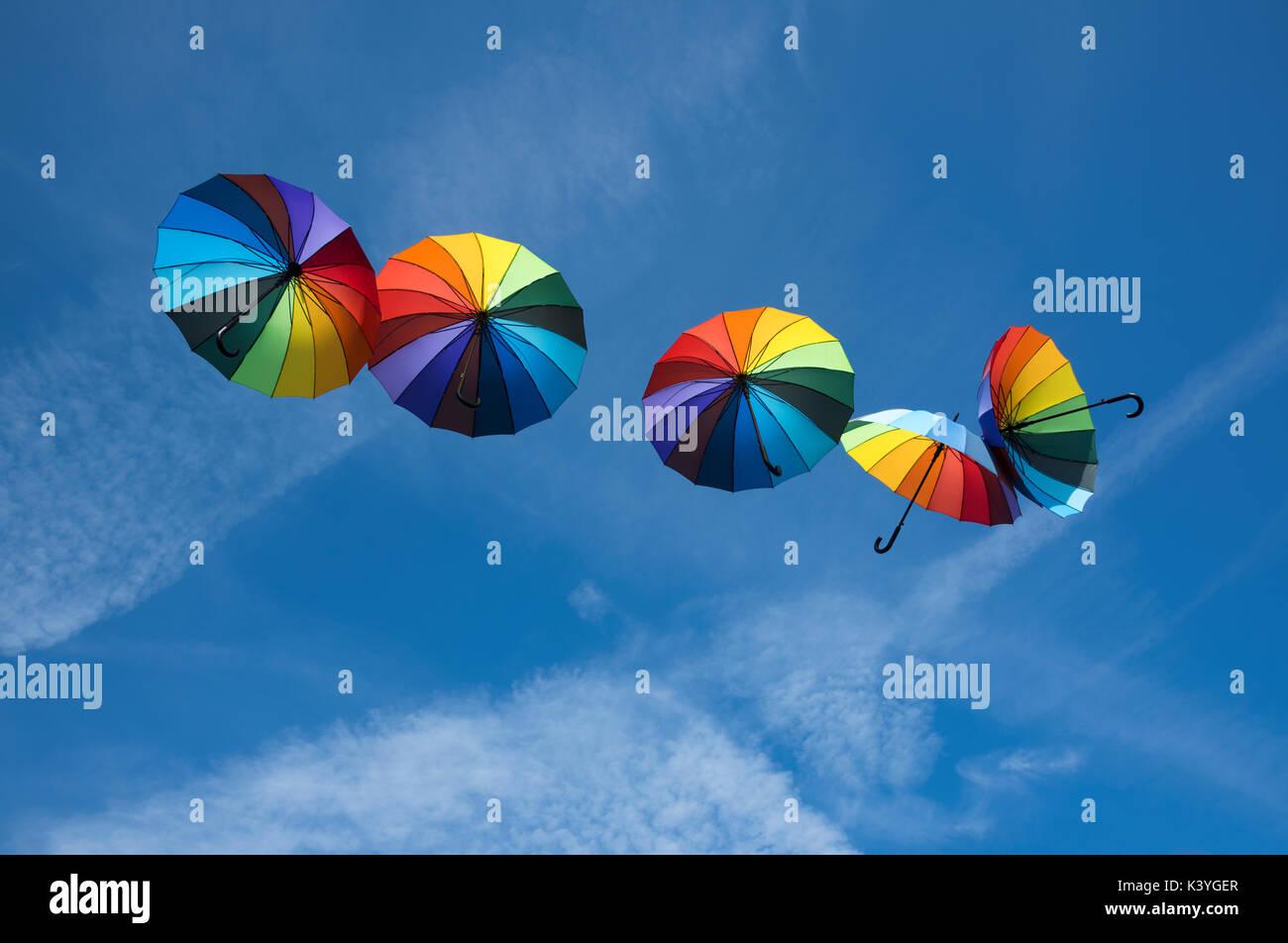Bunte Sonnenschirme floating im blauen Himmel Stockbild