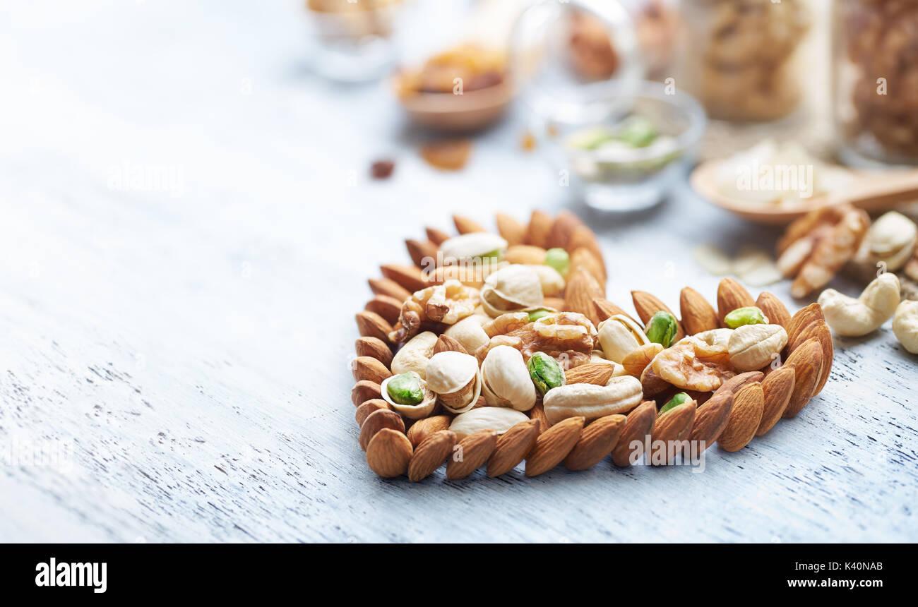 Gemischte Nüsse bilden ein Herz - Form auf weiß lackierten Holz Hintergrund Stockbild
