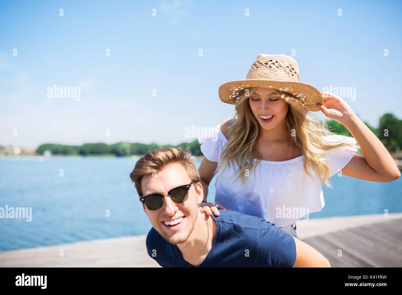 Ein Foto der Jungen, glückliches Paar auf Urlaub. Der Mann ist mit seiner Freundin ein Huckepack. Stockbild