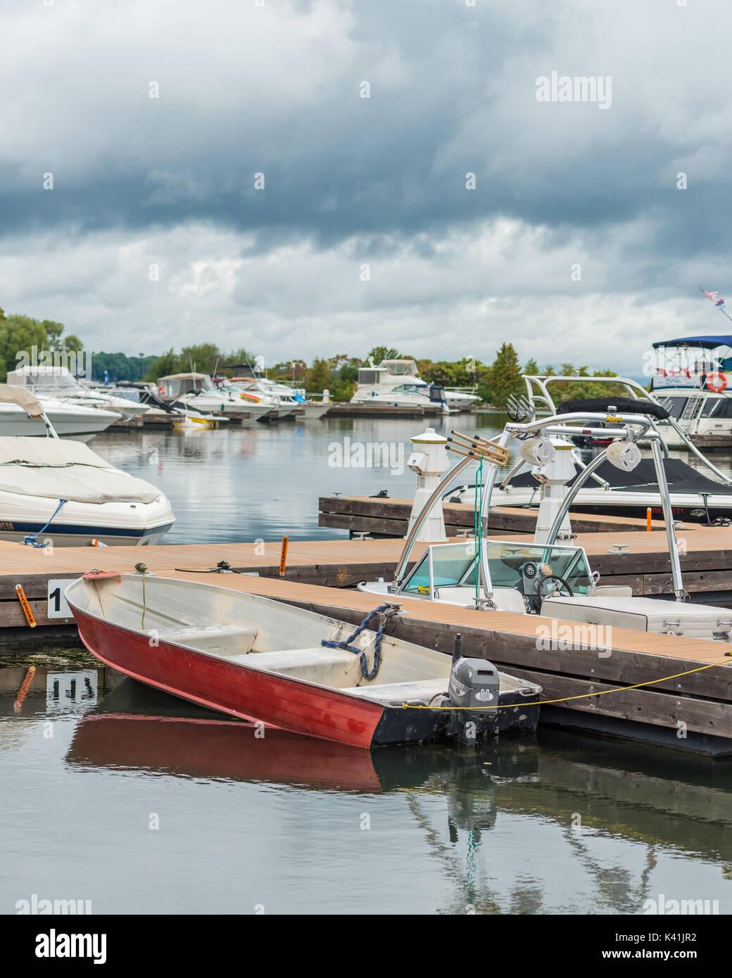 Kleine rote außenliegende Motorboot ist bei größeren teurer Yachten in Orillia Ontario zeigen, dass Bootfahren kann von allen genossen werden angedockt. Stockfoto