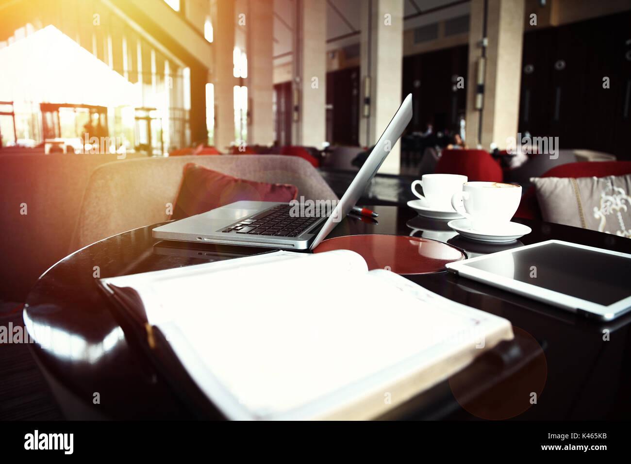 Offen Laptop und Tasse Kaffee liegen auf einem hölzernen Tisch im ...