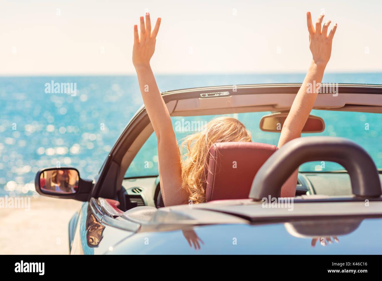 Glücklich und sorgenfrei Frau im Auto am Strand Stockbild