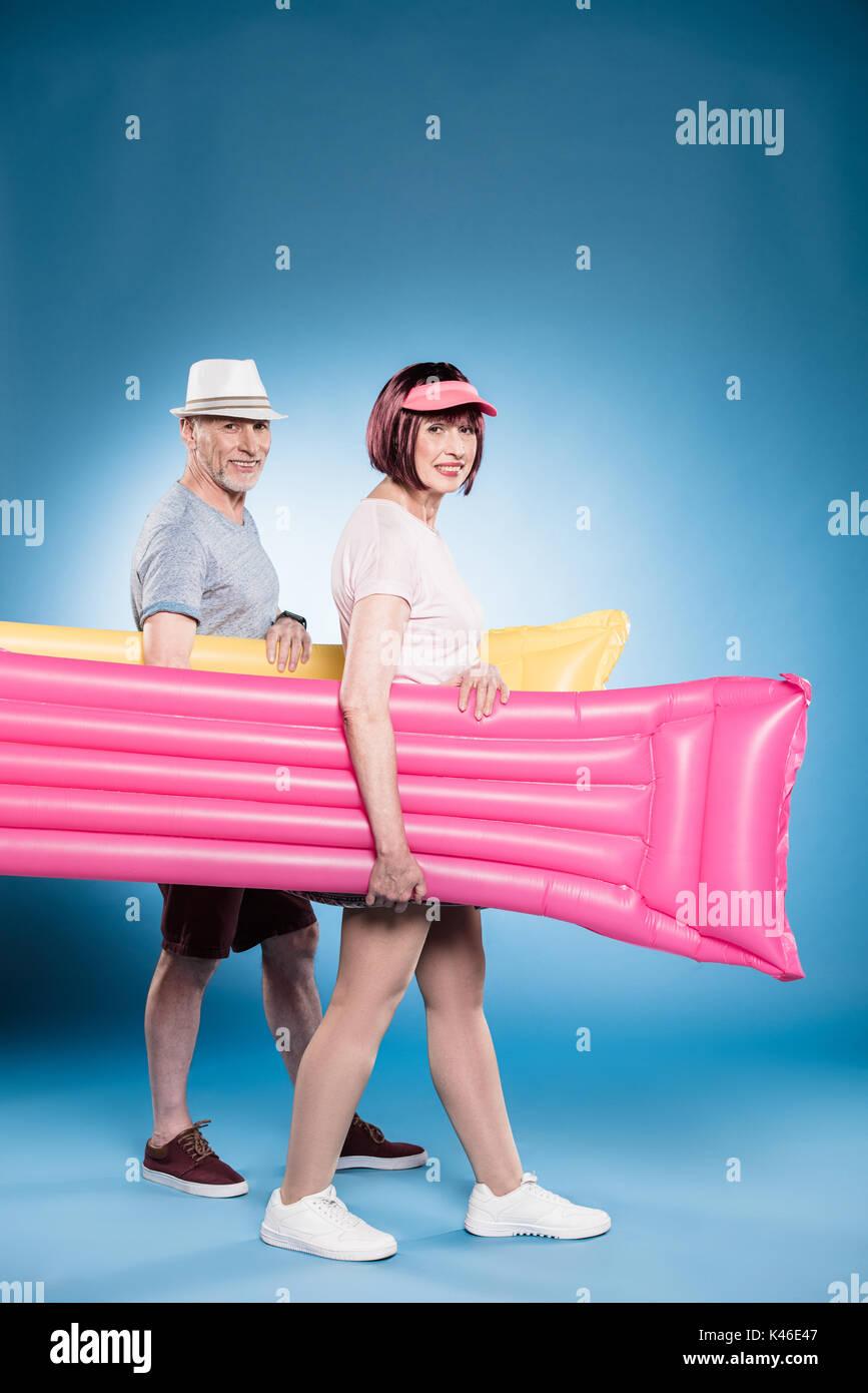 Lächelnd senior Paar an Kamera und halten schwimmen Matratzen beim Spaziergang Stockbild