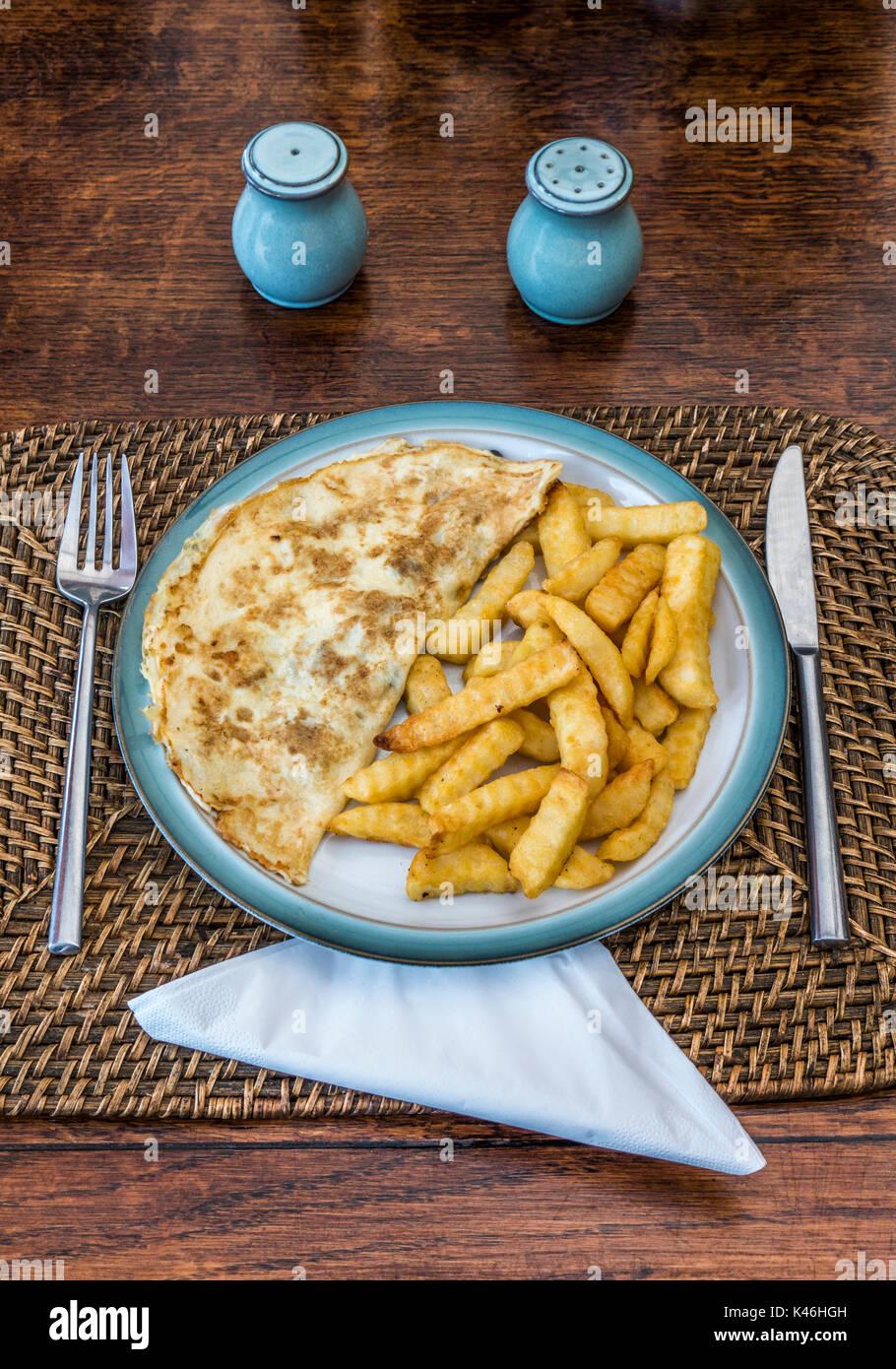 Omelette und gewellter schneiden Sie die Kartoffeln abbrach, auf einem denby Steingut Teller, mit begleitenden Servietten, Salz- und Pfefferstreuer, Edelstahl Messer und Gabel. Stockbild