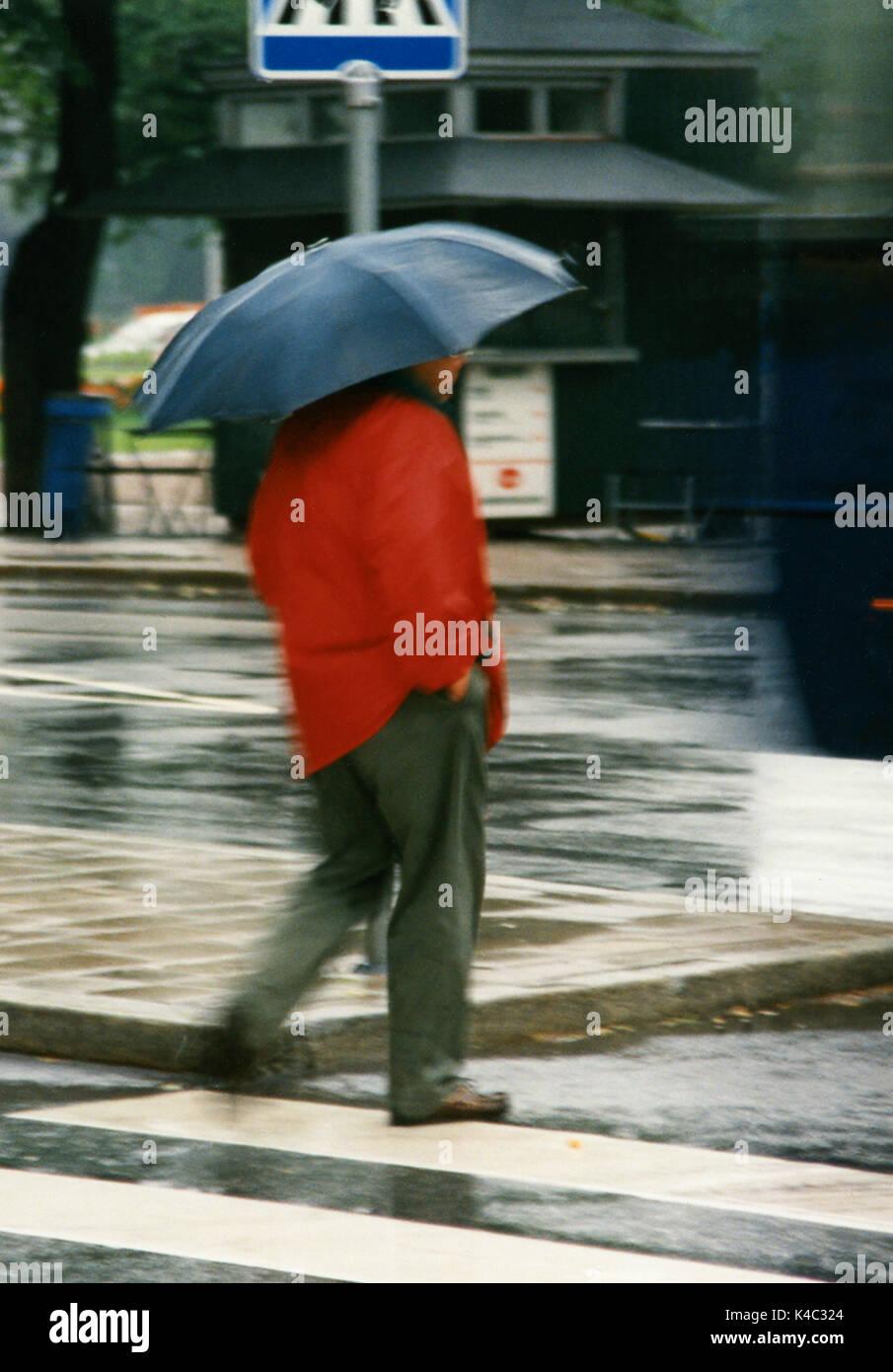 Mann unter dem Dach im Sommer Regen 2008 Stockbild