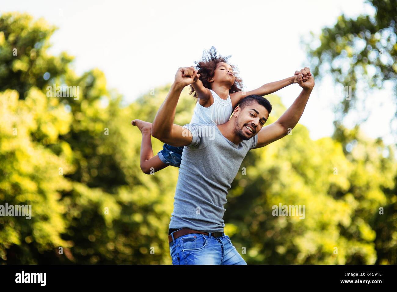 Porträt der jungen Vater, der seine Tochter, die auf dem Rücken Stockbild