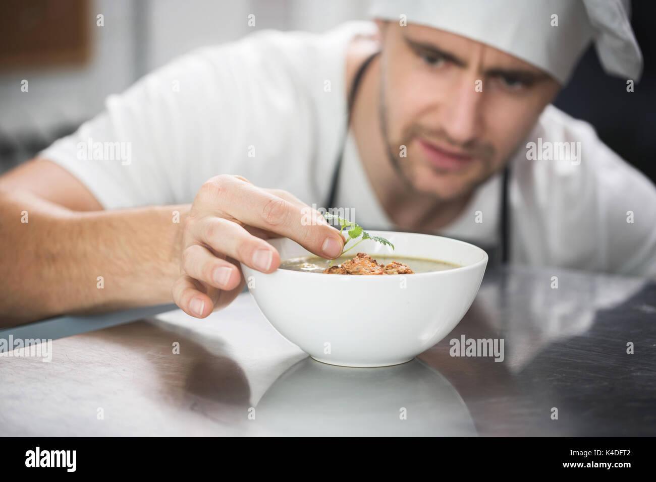 Close up Portrait von Chef dekorieren Suppe in der Küche Stockbild