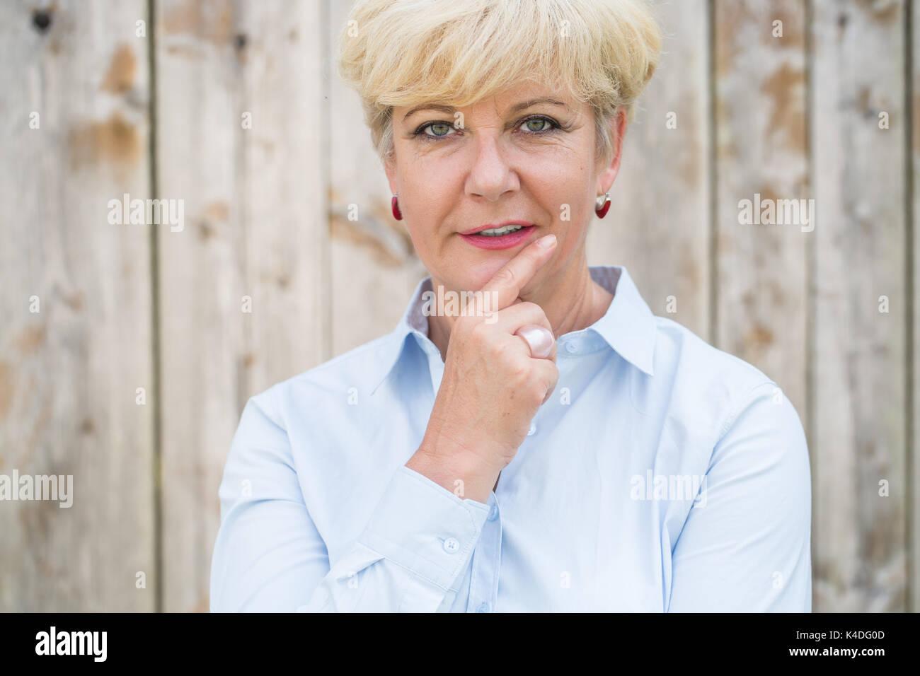 Porträt eines aktiven älteren Frau an der Kamera mit einem Kugelschreiber Stockbild