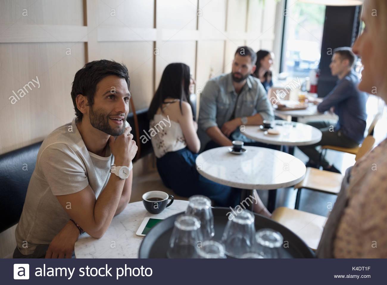 Männliche Kunden im Gespräch zu Kellnerin im Cafe Stockbild
