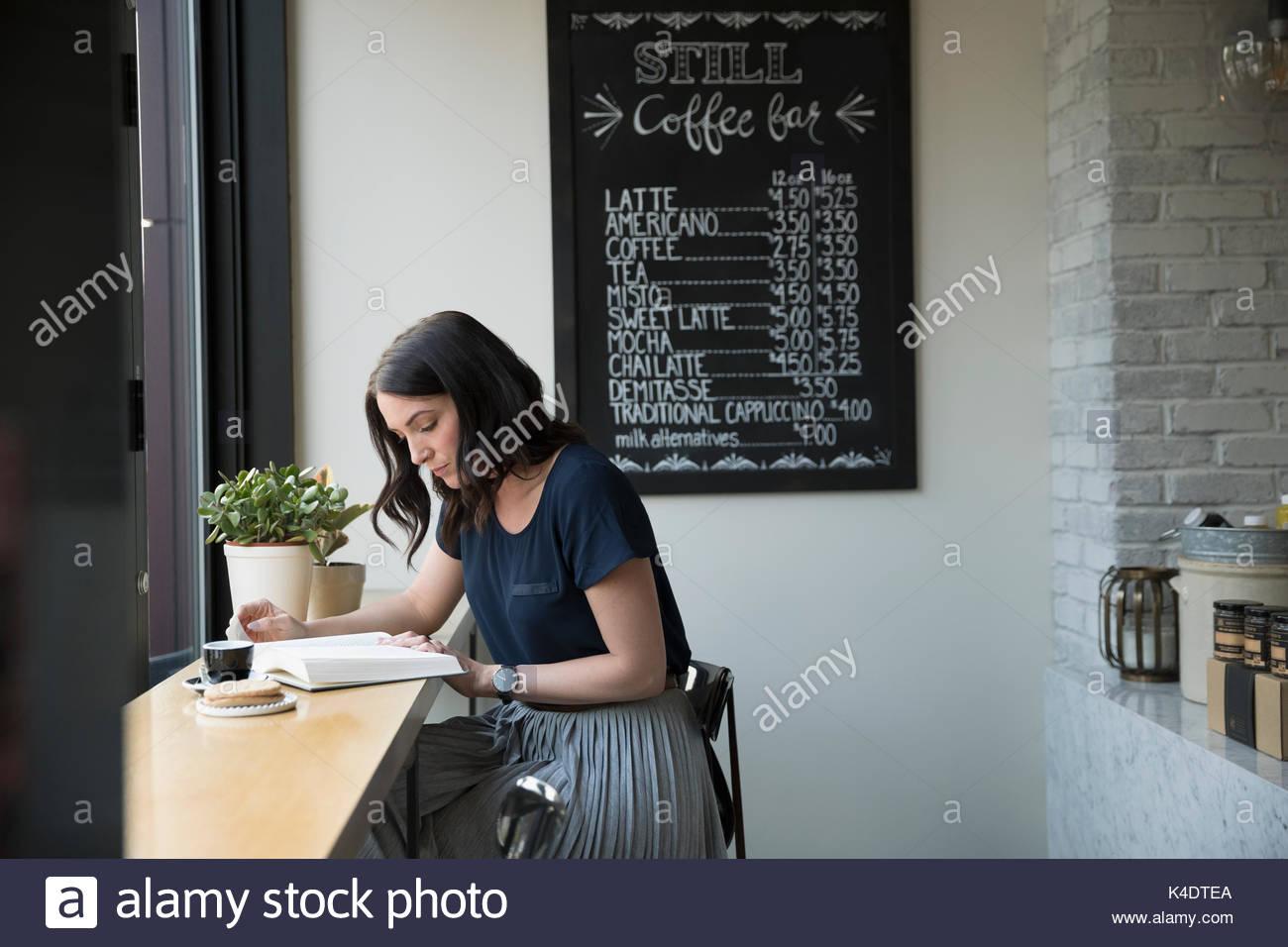 Frau mit Buch und Kaffee trinken an der Theke im Cafe Stockbild