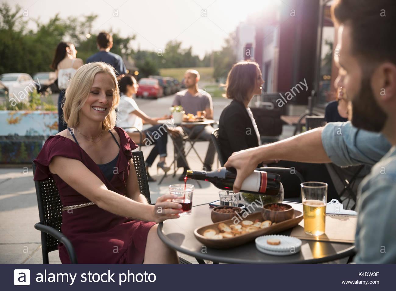 Man gießt Rotwein für Freundin am Sidewalk Cafe Stockbild