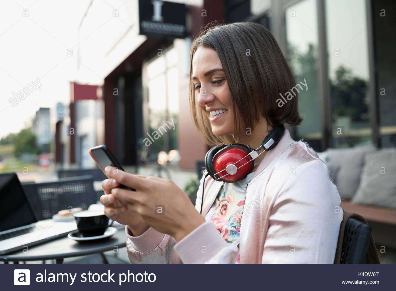 Lächelnd brünette Frau mit Kopfhörer SMS mit Handy im Straßencafé Stockbild