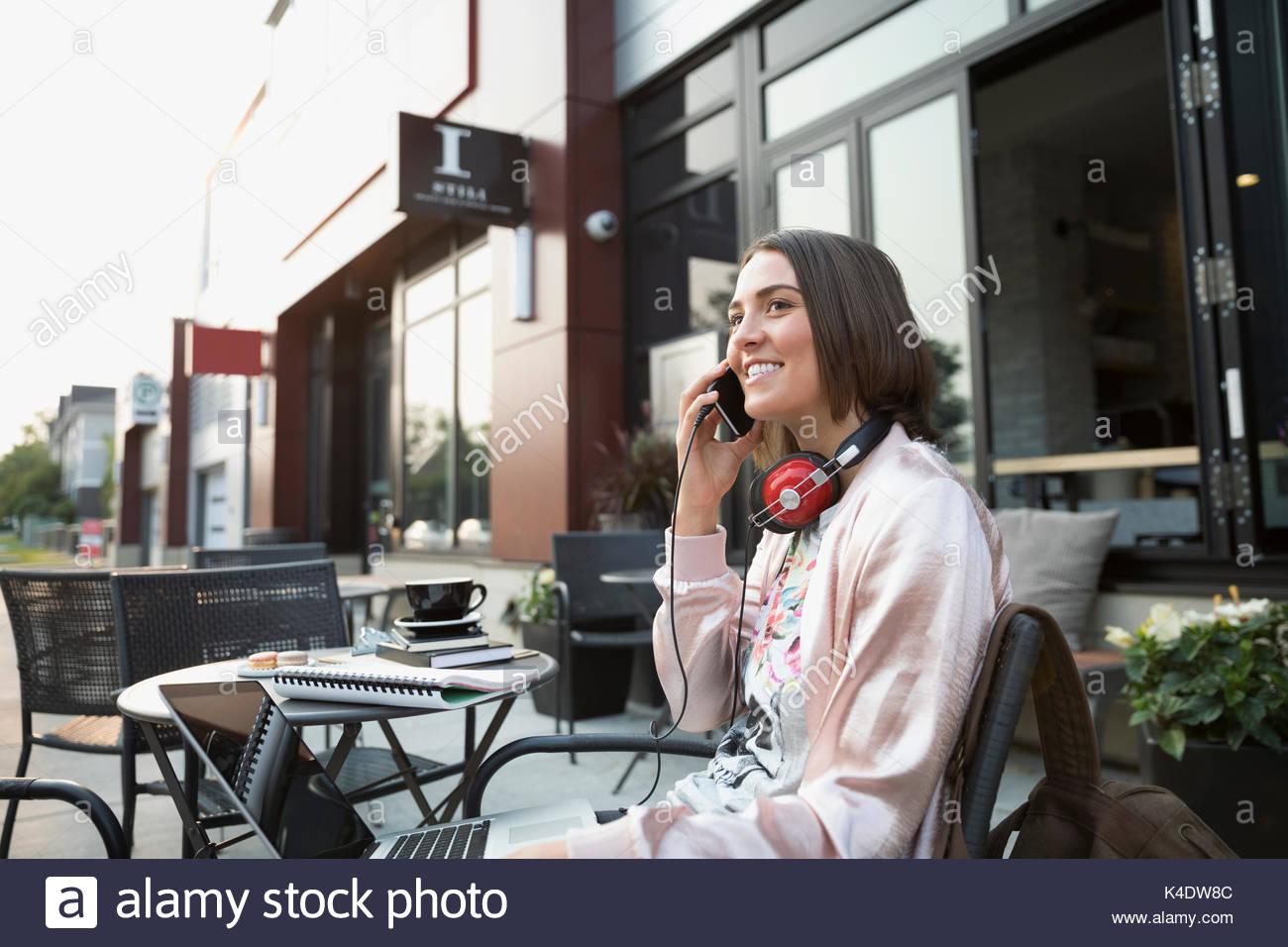 Lächelnd brünette Frau mit Kopfhörer Gespräch am Handy mit Laptop im Straßencafé Stockbild