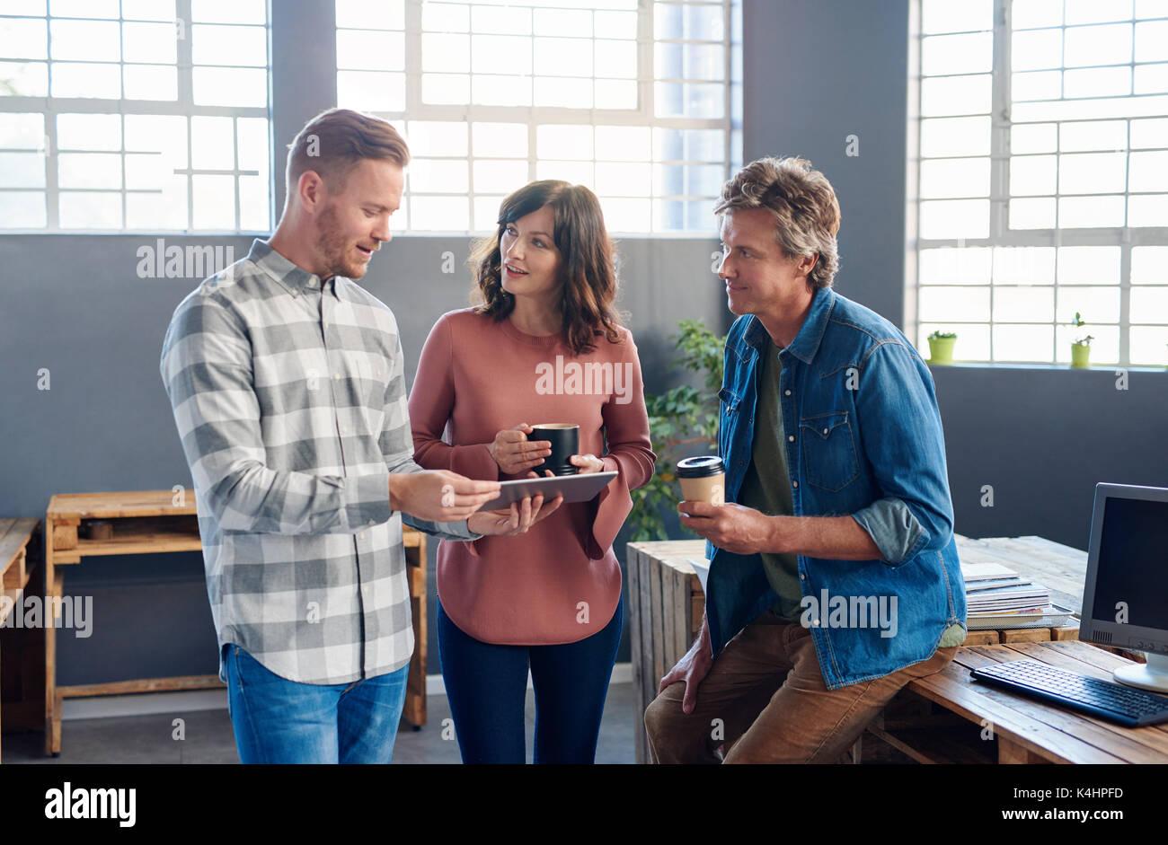 Drei Lachelnd Buro Kollegen Sprechen Uber Ein Digitales Tablette