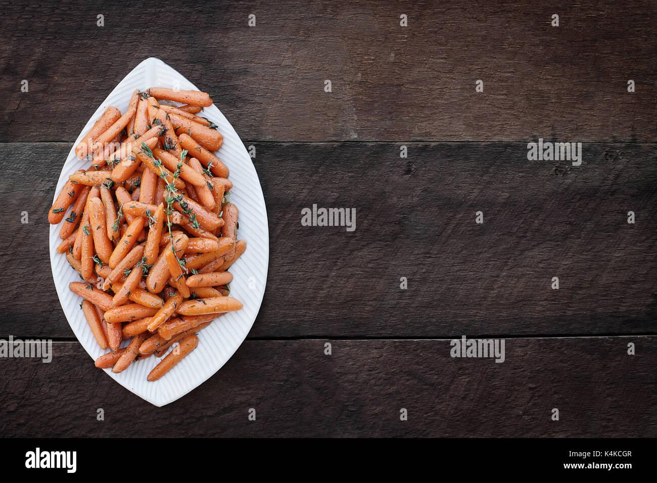 Honig glasierte Karotten und alten hölzernen Löffel. Bild geschossen von oben in flatlay Stil. Stockbild