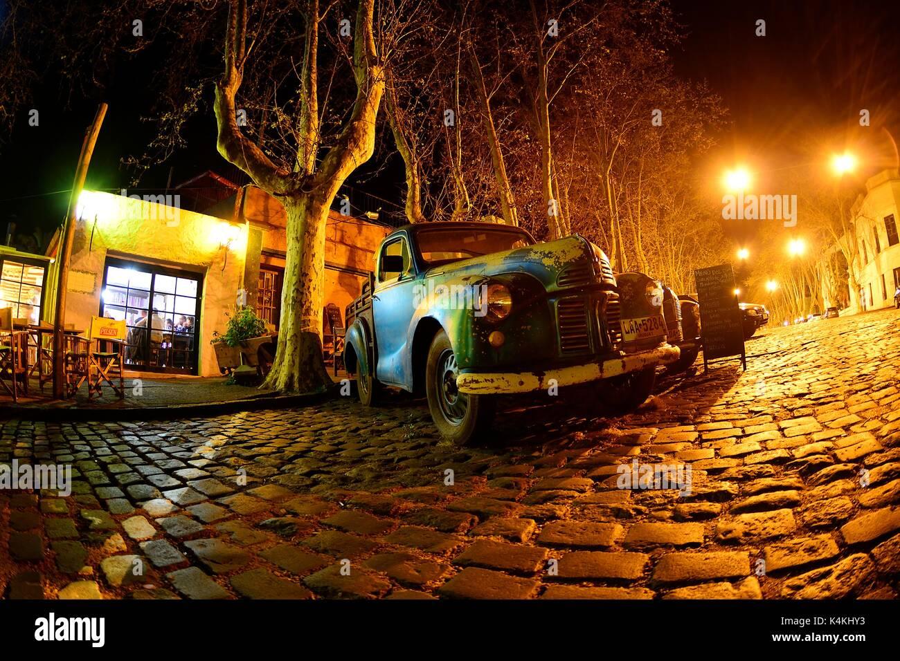Oldtimer Autos auf der Straße mit Kopfsteinpflaster, Avenida Gral Flores in der Nacht, Colonia del Sacramento, Uruguay Stockbild