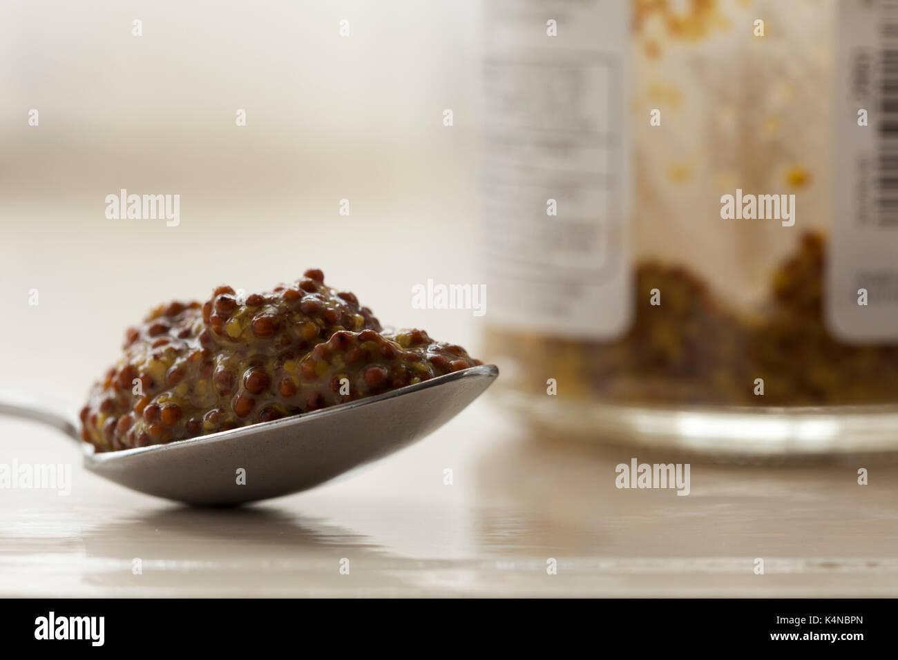 Einen gehäuften Teelöffel vollkorn Senf mit dem Glas Senf jar, die Bestandteil des unscharf Hintergrund. In natürlichem Licht gedreht. Stockbild