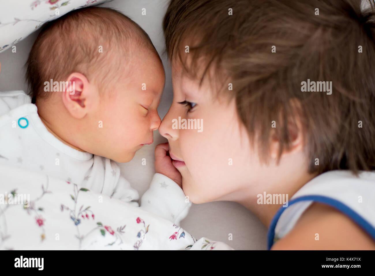 Schöne junge, umarmen mit Zärtlichkeit und sein neugeborenes Baby Bruder Pflege zu Hause. Familie Liebe Glück Konzept Stockfoto