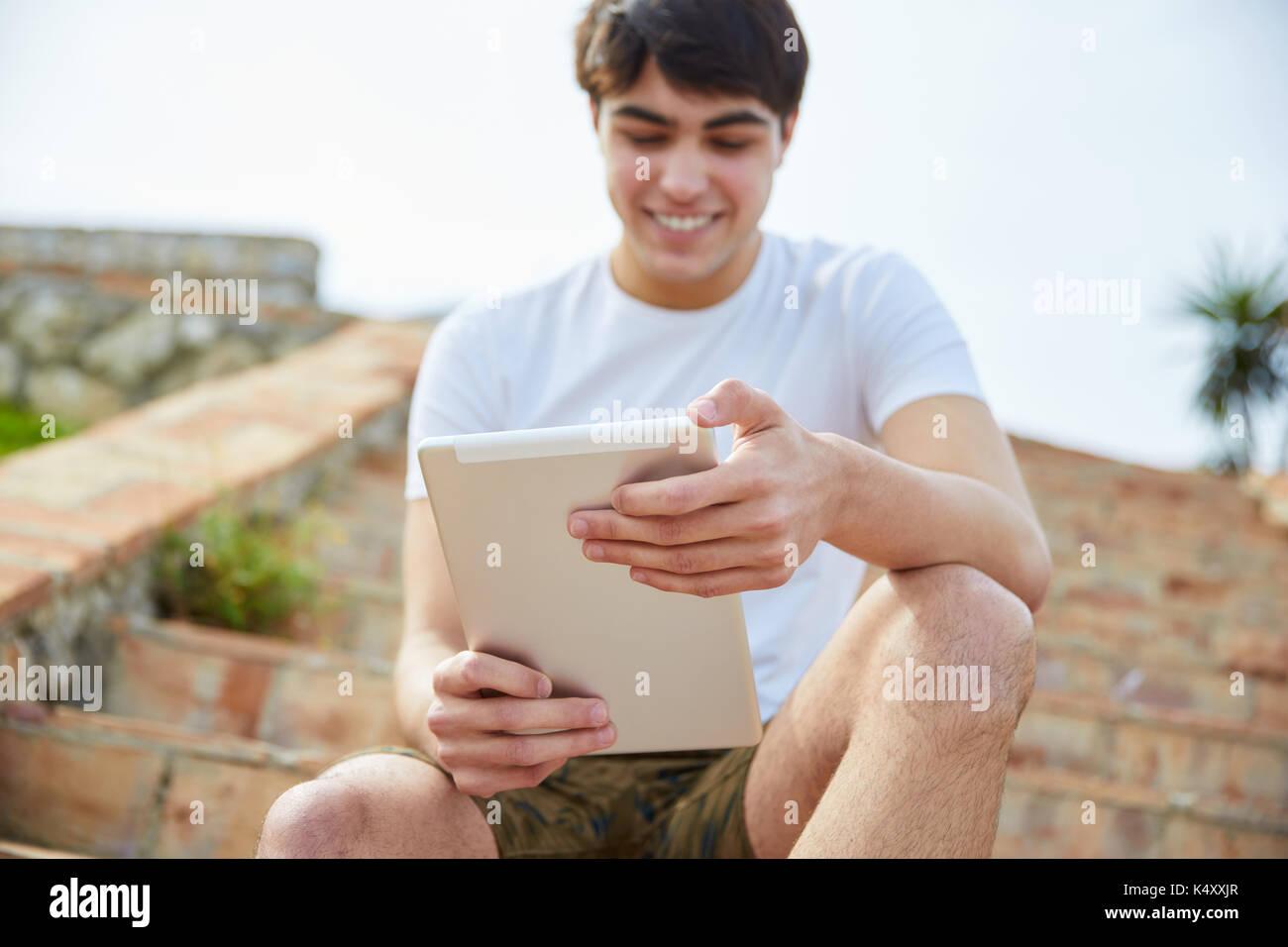 Porträt der jungen glücklich Mann sitzt auf der Treppe außen mit Tablet Stockbild