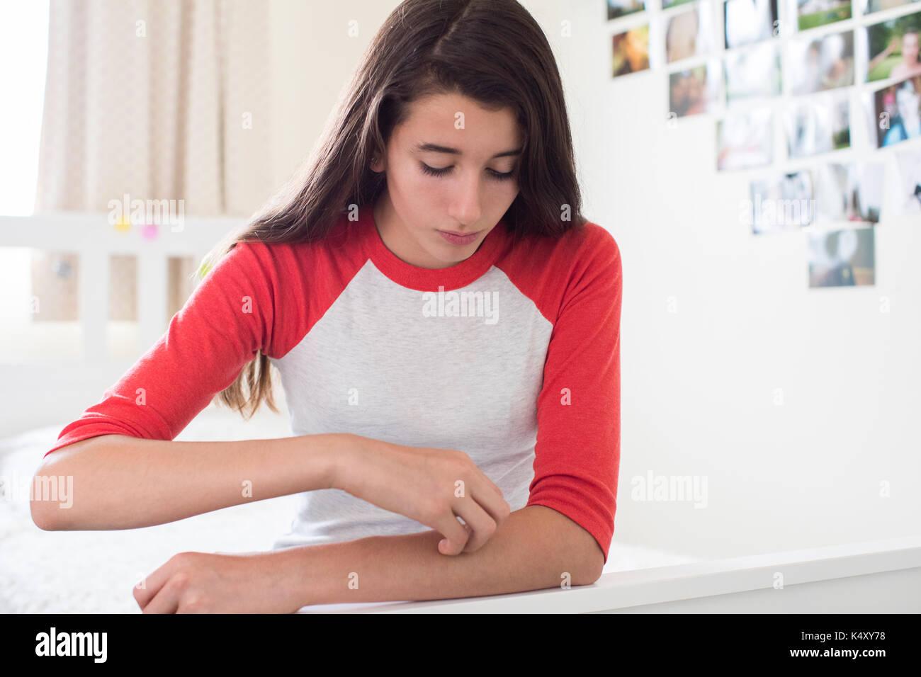 Junges Mädchen sitzen im Schlafzimmer Kratzen Arm Stockbild