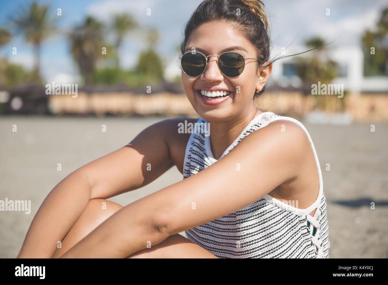 Porträt der schöne junge Frau sitzt am Strand lachen Stockbild
