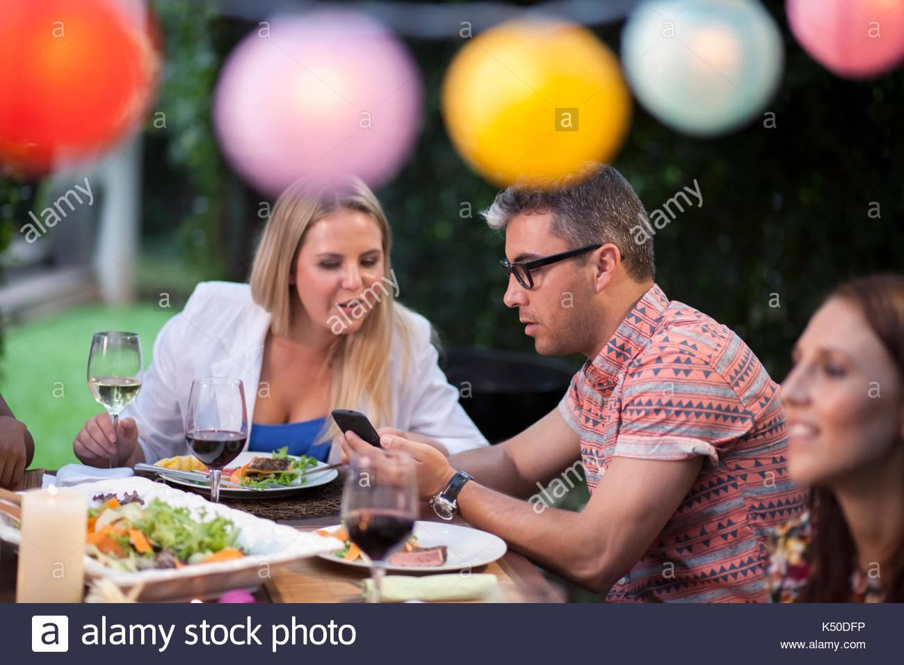 Zwei Freunde, die an einem Telefon am Tisch Stockbild