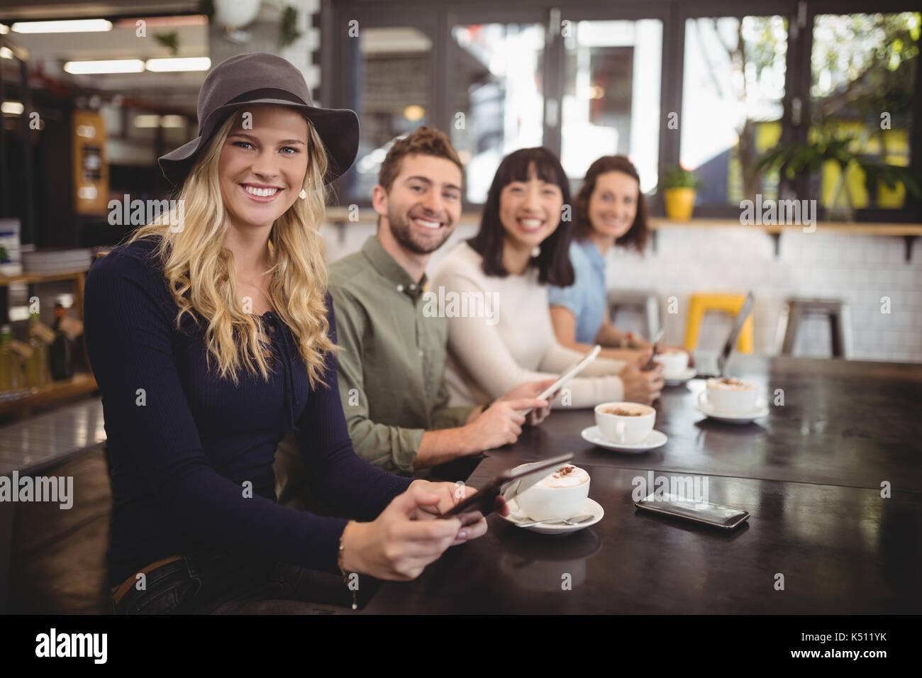 Portrait von lächelnden multi-ethnische Freunde sitzen mit Kaffeetassen und Handys am Tisch im Cafe Stockfoto