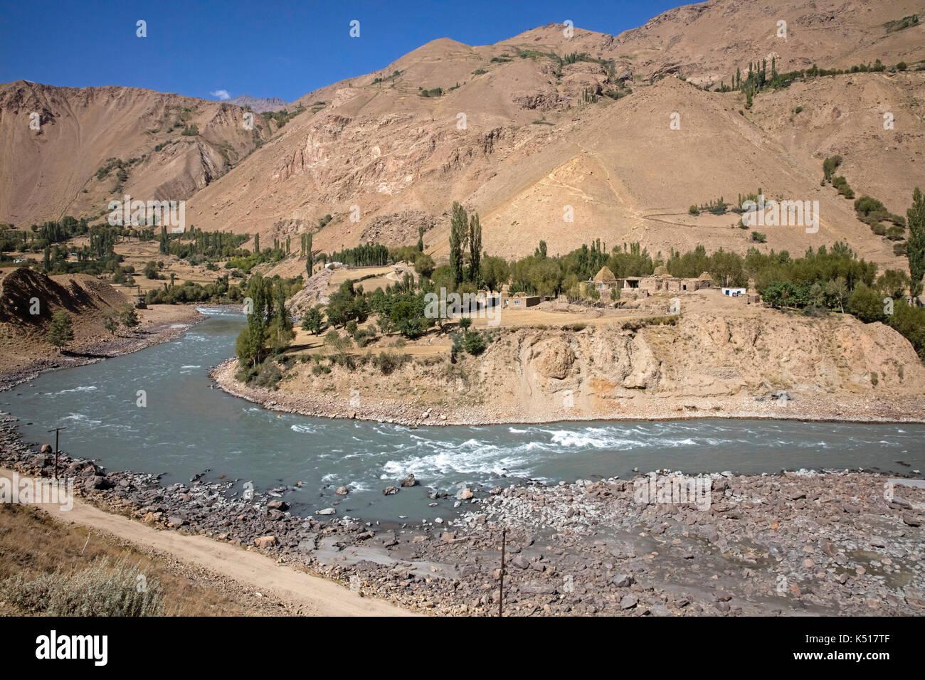 Wenig afghanischen Dorf und den Pamir Highway/M41 entlang der Pamir Fluss bildet die Grenze zwischen Tadschikistan und Afghanistan Stockbild