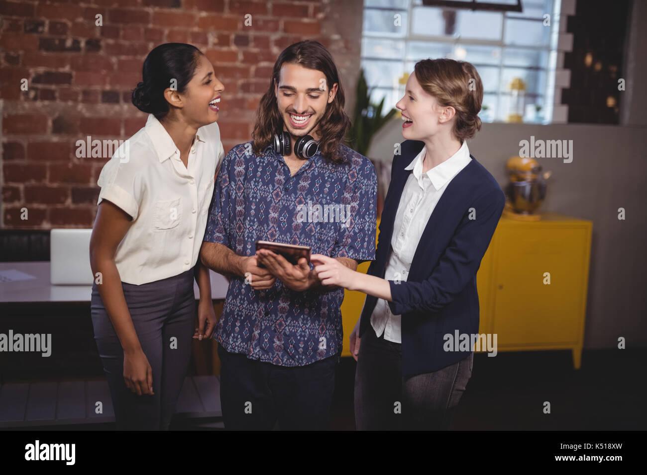 Fröhlicher junger Freunde stehend mit digitalen Tablet im Coffee Shop Stockbild