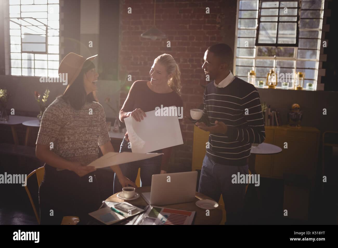 Fröhliche kreatives Team stehen mit Papieren im Coffee Shop Stockbild