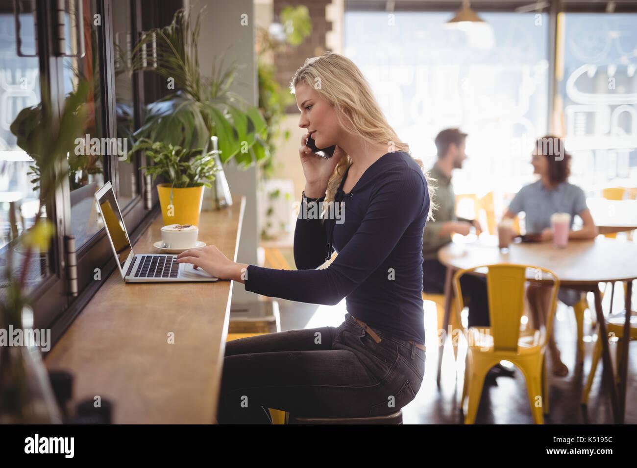 Seitenansicht der junge blonde Frau Gespräch am Handy mit Laptop im Cafe Stockbild