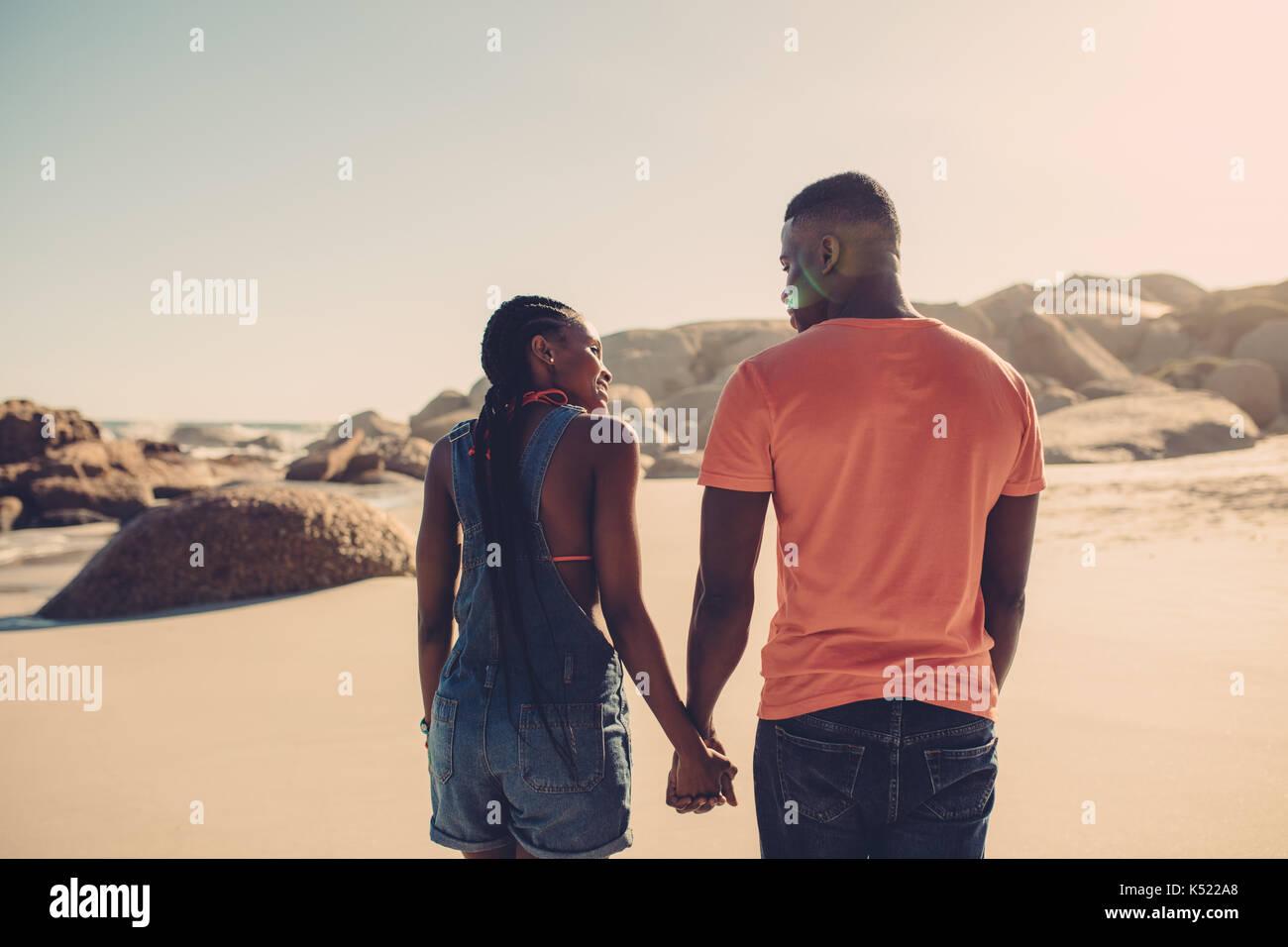 Afrikanische amerikanische Paar Hände halten und zu Fuß am Strand entlang. Mann und Frau in der Liebe ein Spaziergang Stockfoto