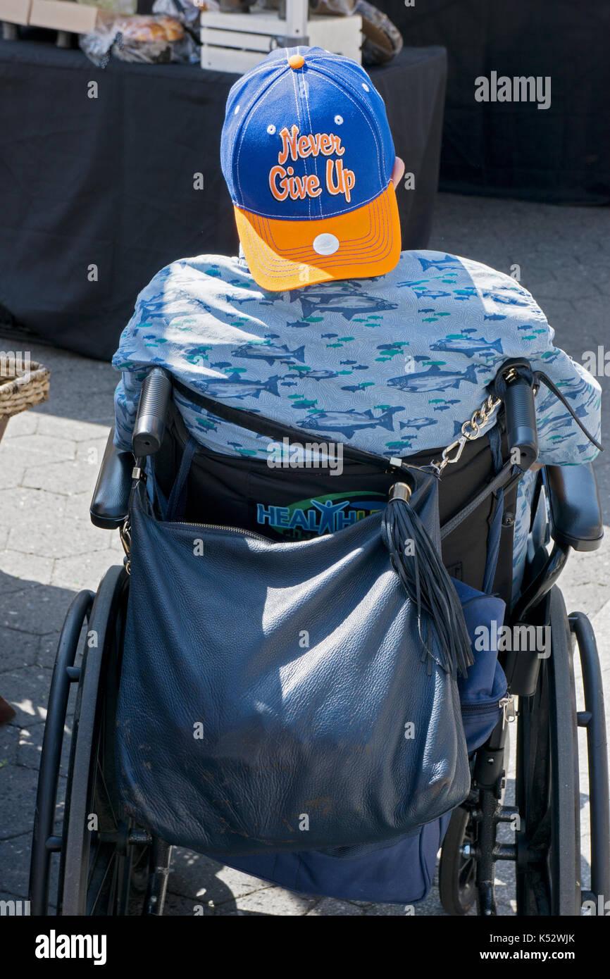 """Ein Mann im Rollstuhl trägt eine Kappe mit dem Slogan """"Nie die Hoffnung geben' in Lower Manhattan, New York City. Stockbild"""