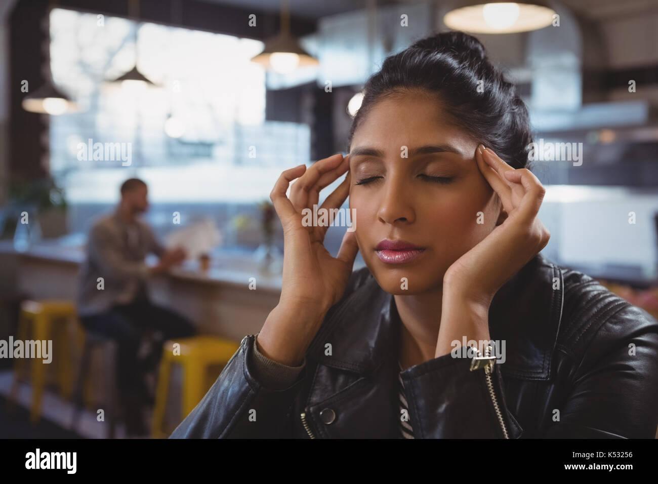 Junge Frau leidet unter Kopfschmerzen mit Freund im Hintergrund im Cafe Stockbild