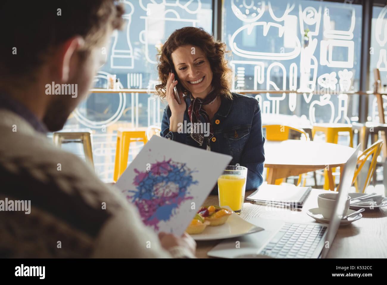 Mann hält Papier mit Malerei von jungen Frau am Telefon sprechen im Cafe Stockbild