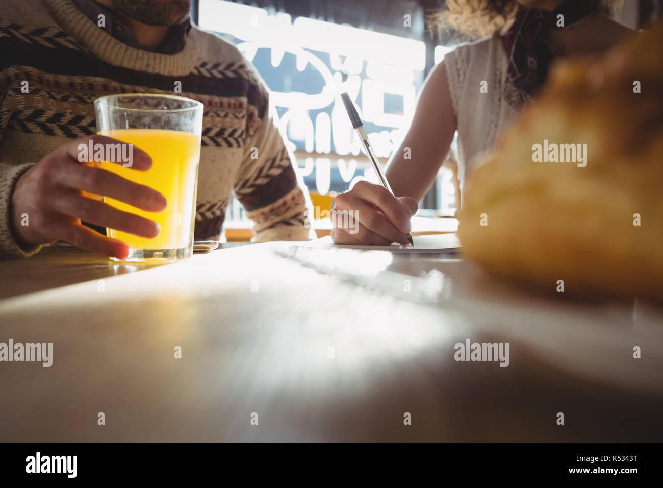 Mittelteil der jungen Mann mit Frau, Saft am Tisch im Cafe Stockbild