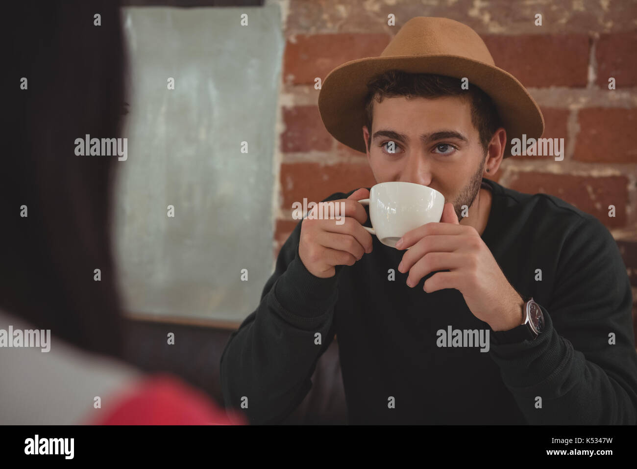Junger Mann mit Freundin suchen beim Trinken Kaffee im Cafe Stockbild