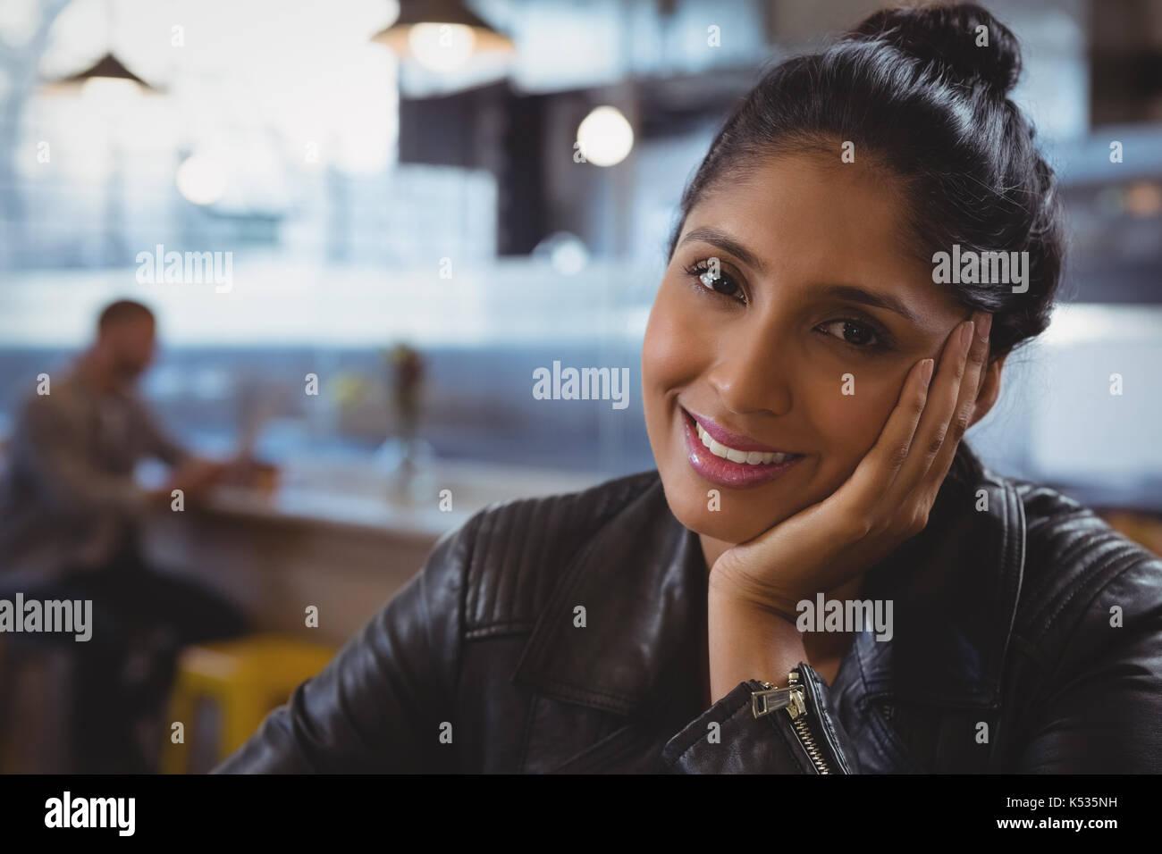 Close-up Portrait von lächelnde Frau mit Freund im Hintergrund im Cafe Stockbild