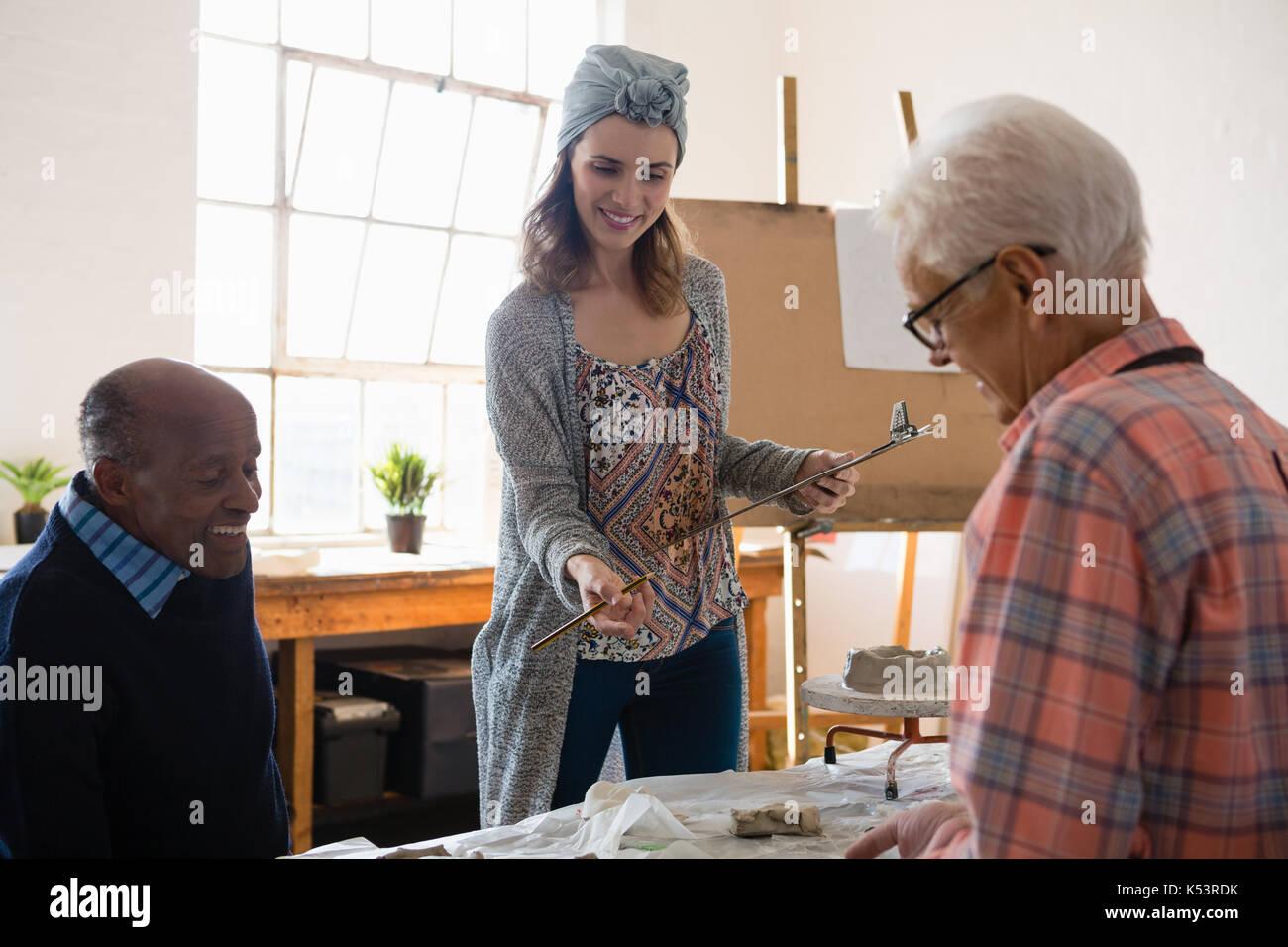 Lächelnd weibliche Holding Zwischenablage beim Gespräch mit männlicher Künstler im Kunstunterricht Stockbild