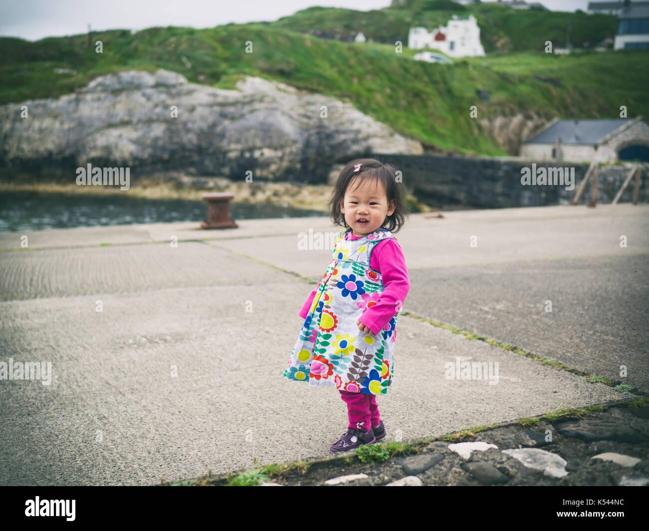 Baby Mädchen zu Fuß in den kleinen Hafen, Nordirland Stockfoto