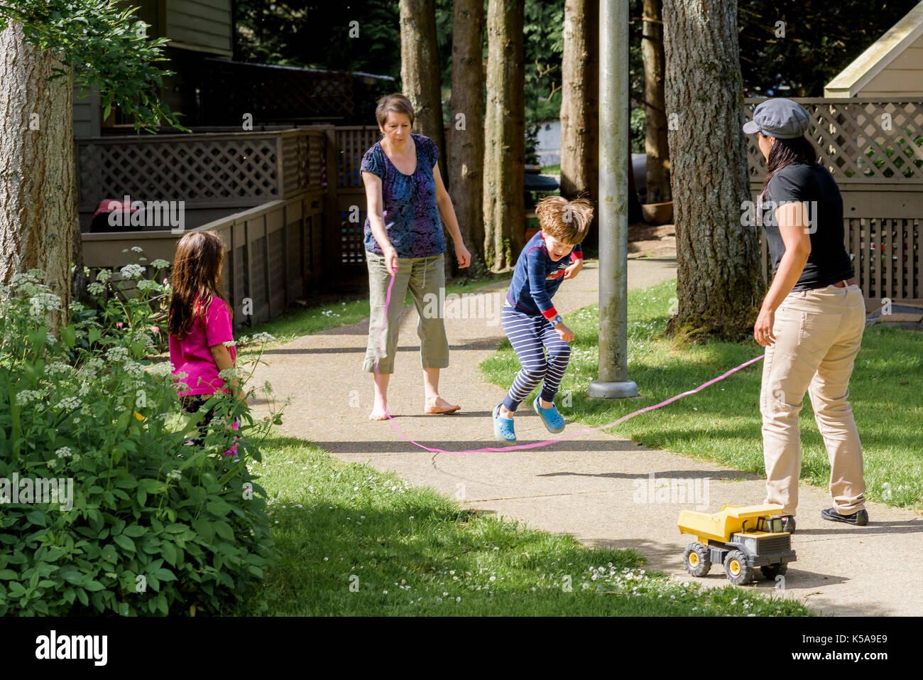 Junge Junge spielt Springseil Spiel mit Erwachsenen. Stockbild