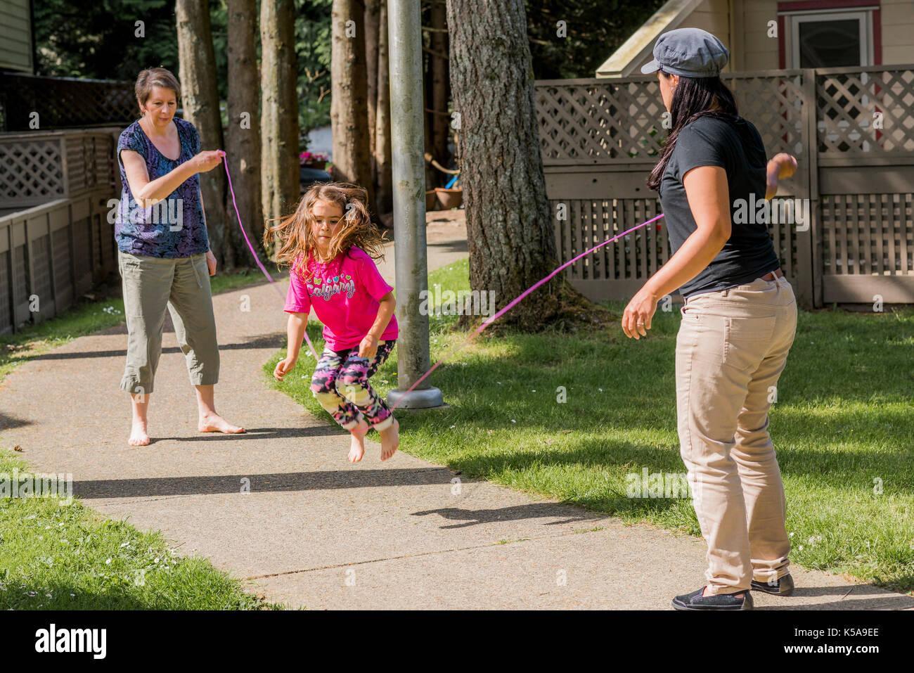 Junge Mädchen spielen Springseil Spiel mit Erwachsenen. Stockbild