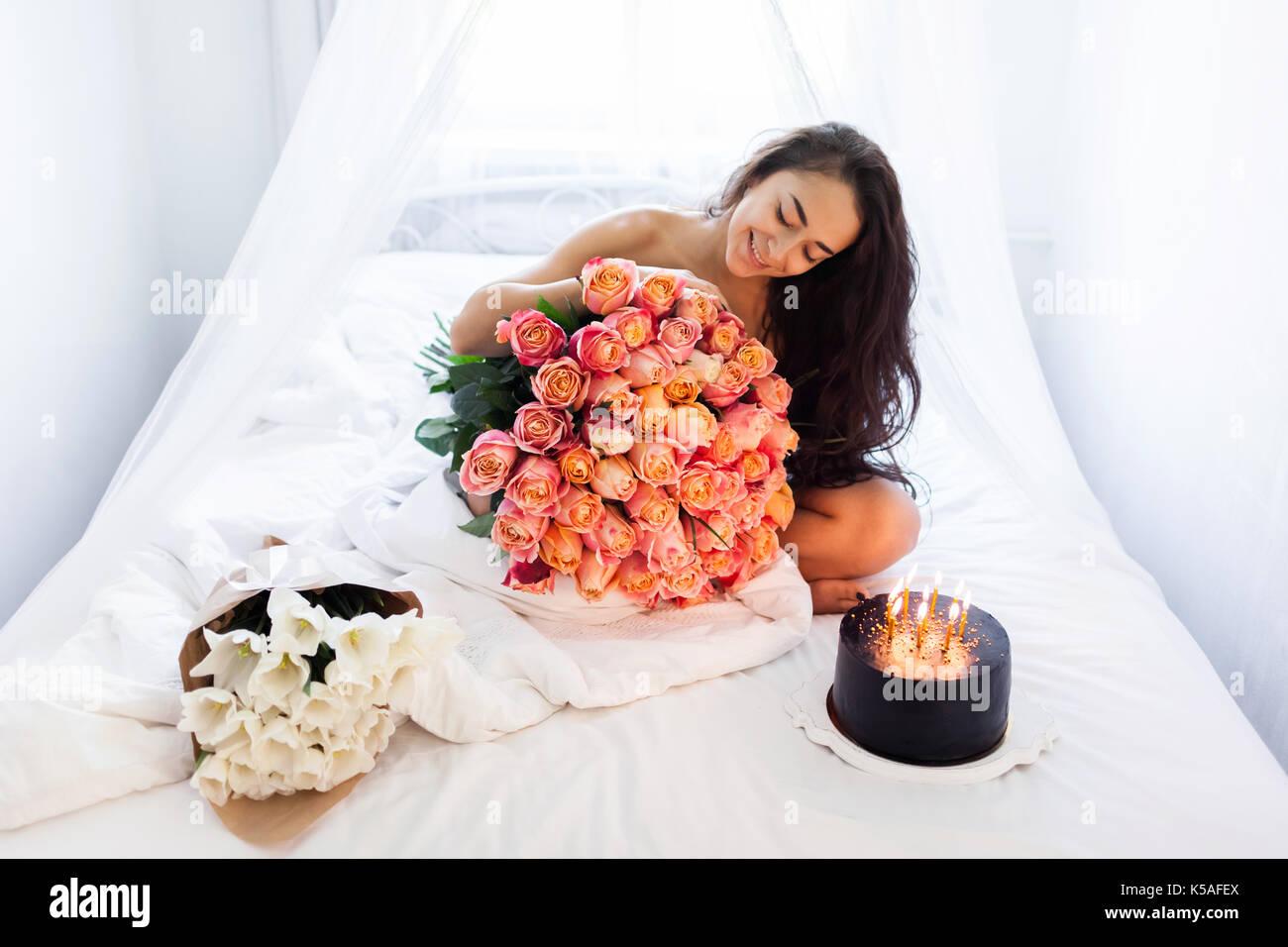Hervorragend Geburtstag Morgen Junge Frau Mit Riesigen Blumenstrauß Aus Rosen Und  Leckeren Kuchen Mit Kerzen Auf Weißen Bett