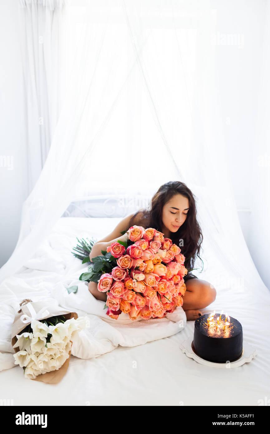 Elegant Geburtstag Morgen Junge Frau Mit Riesigen Blumenstrauß Aus Rosen Und  Leckeren Kuchen Mit Kerzen Auf Weißen Bett
