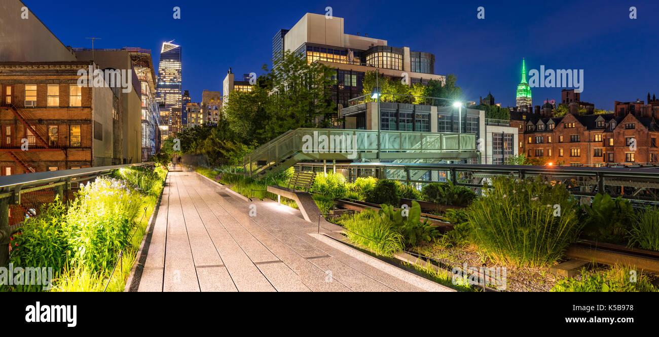 Panoramablick auf die High Line Promenade in der Dämmerung mit City lights und beleuchtete Hochhäuser. Stockbild